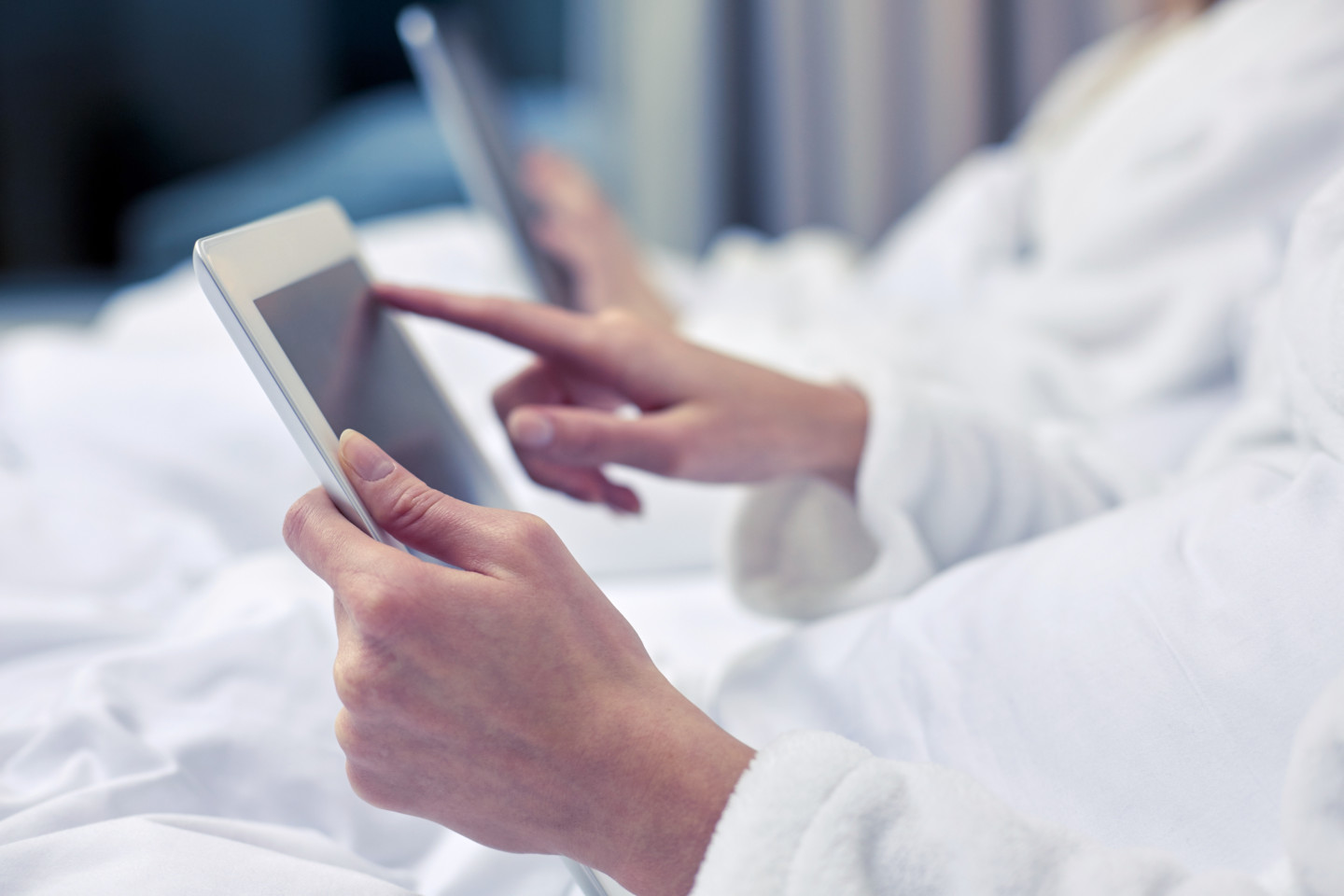 close up of woman hands in bathrobe with tablet pc